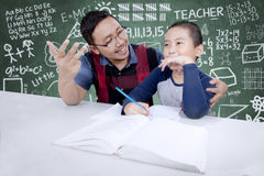 Teacher helping his student to count Royalty Free Stock Photography