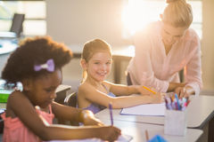 Teacher helping kids with their homework in classroom Royalty Free Stock Image
