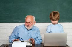 Teacher helping kids with their homework in classroom at school. Dad son are concentrated on the problem. Grandfather. And grandson. Tutoring royalty free stock photos