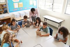 Teacher helping kids using tablets in lesson, elevated view stock images