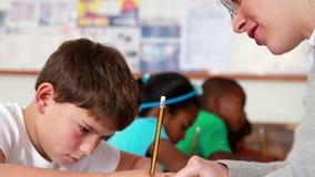 Teacher helping a little boy during class. In elementary school stock video footage