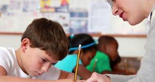 Teacher helping a little boy during class. In elementary school stock footage