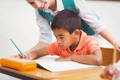 Teacher helping a little boy during class Stock Photos