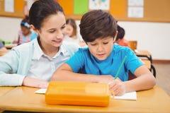 Teacher helping a little boy during class Stock Photo