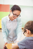 Teacher helping a little boy during class Royalty Free Stock Image