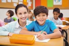Teacher helping a little boy during class Stock Images