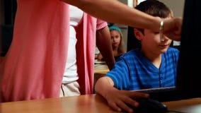 Teacher helping little boy in computer class. In elementary school stock video footage