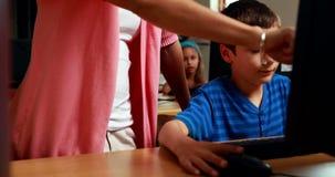 Teacher helping little boy in computer class. In elementary school stock video