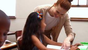 Teacher helping a little girl during class stock video