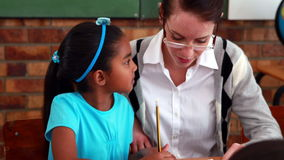 Teacher helping a little girl during class. In elementary school stock video footage