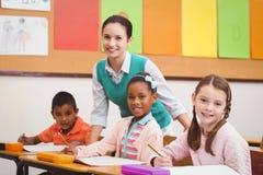 Teacher helping a little girl during class Stock Images