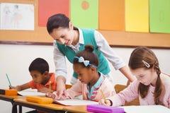 Teacher helping a little girl during class Stock Photography