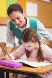 Teacher helping a little girl during class Stock Photo