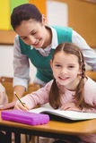 Teacher helping a little girl during class Royalty Free Stock Image
