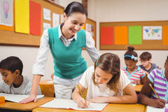 Teacher helping a little girl during class Royalty Free Stock Photo