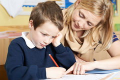 Teacher Helping Male Elementary School Pupil With Problem Royalty Free Stock Image