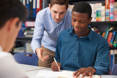 Teacher Helping Male Pupil In Class Royalty Free Stock Photography
