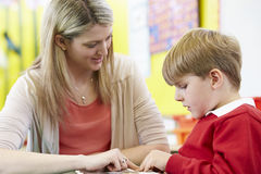 Teacher Helping Male Pupil With Reading At Desk Stock Image