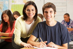 Teacher Helping Male Pupil Studying At Desk In Classroom. Looking At Camera Smiling Stock Photos