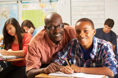 Teacher Helping Male Pupil Studying At Desk In Classroom. Looking At Camera Smiling Stock Images