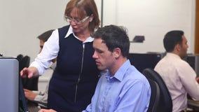 Teacher helping mature student in computer class stock video footage