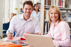 Teacher Helping Mature Student With Studies In Library Stock Photo