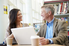 Teacher Helping Mature Student With Studies In Library Stock Photography