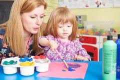Teacher Helping Pre School Child In Art Class. Teacher Helps Pre School Pupil In Art Class royalty free stock photography