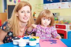 Teacher Helping Pre School Pupil In Art Class Stock Images