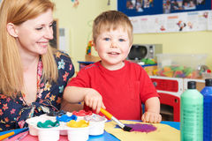 Teacher Helping Pre School Pupil In Art Class. Teacher Helps Preschool Child In Art Class stock photos