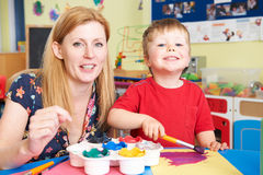 Teacher Helping Preschool Child In Art Class. Teacher Helps Preschool Child In Art Class stock photo