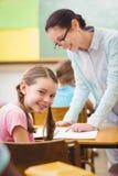 Teacher helping a pupil during class Stock Photos