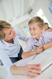 Teacher helping pupil in class. Teacher helping pupil with reading in class Stock Photo