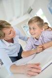 Teacher helping pupil in class Stock Photo