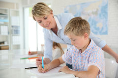 Teacher helping pupil in class. Teacher helping pupil with writing in class Royalty Free Stock Photo