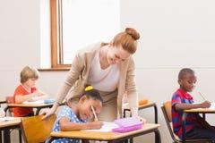 Teacher helping pupil in classroom Stock Photos