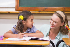 Teacher helping pupil in classroom Stock Image