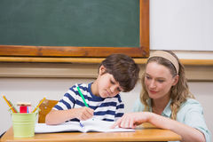 Teacher helping pupil in classroom Royalty Free Stock Photo