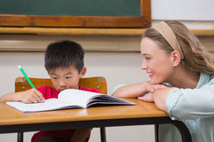 Teacher helping pupil in classroom Stock Photography