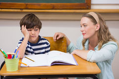 Teacher helping pupil. At elementary school Stock Photo