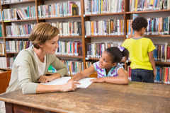 Teacher helping pupil in library Stock Photo