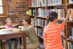 Teacher helping pupil in library Royalty Free Stock Photo