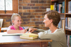 Teacher helping pupil in library. At elementary school Stock Image