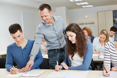 Teacher helping pupil in school Royalty Free Stock Photos