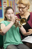 Teacher Helping Pupil To Play Trumpet In Music Lesson. Teacher Helping Pupil To Play Trumpet In Music Class Stock Photo