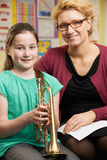 Teacher Helping Pupil To Play Trumpet In Music Lesson. Portrait Of Teacher Helping Pupil To Play Trumpet In Music Lesson Stock Images