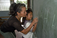 Teacher helping pupil writing on chalkboard. Nicaragua, capital, city Managua: A girl learns to write on a blackboard. Miss Bergstrom, female schoolteacher Royalty Free Stock Photos