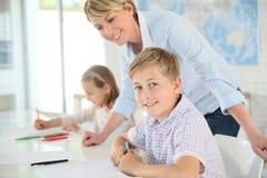 Teacher helping pupils in class Stock Image