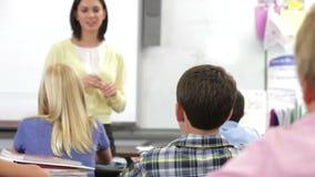 Teacher Helping Pupils In Class stock video