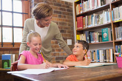 Teacher helping pupils in library Royalty Free Stock Images